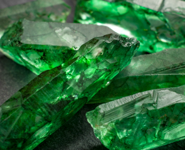 raw emeralds in grey background